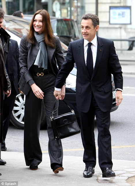 The President grasps his wife's hand as they go to vote in the French regional elections