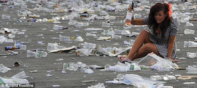 A racegoer, who looks slightly worse for wear, attempts to get up after finding herself sitting on the ground