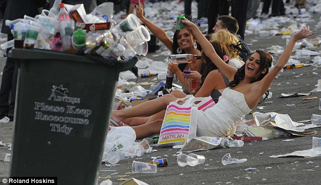 Revellers sit among the rubbish left at Aintree racecourse at the end of the day