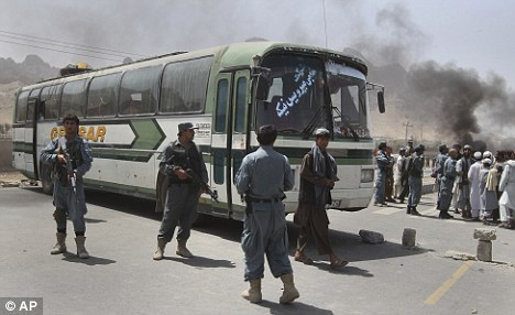 Afghan policemen and protesters stand near a bus after it was fired upon by international troops, killing four people and wounding 18 others