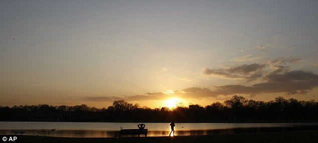 Rare sight: Visitors to London's Kensington Gardens enjoy a sunset without planes in the sky. The grounding of planes across Europe is likely to effect the temperature