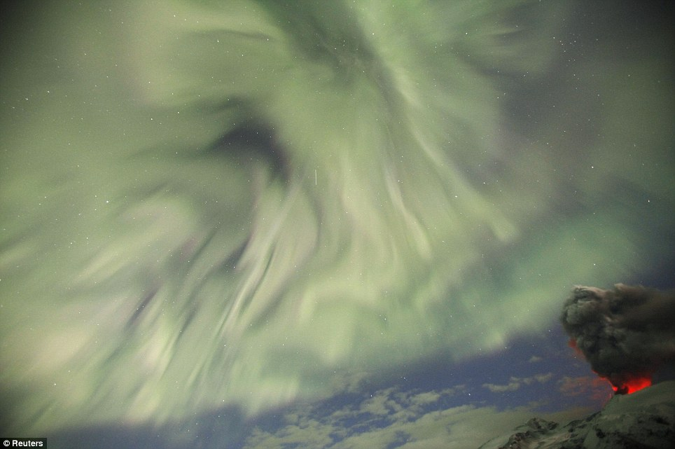The aurora borealis, pictured above the volcano, is created by the sun's super hot atmosphere, which blasts particles into the protective magnetic field surrounding the Earth
