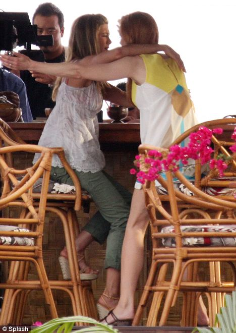 Old friends: Aniston and Kidman films an over-the-top greeting at the beach bar