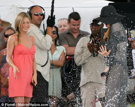 Amused: Jennifer Aniston can't contain her giggles as Nicole Kidman gets a soaking from a swimmer by a pool in Maui