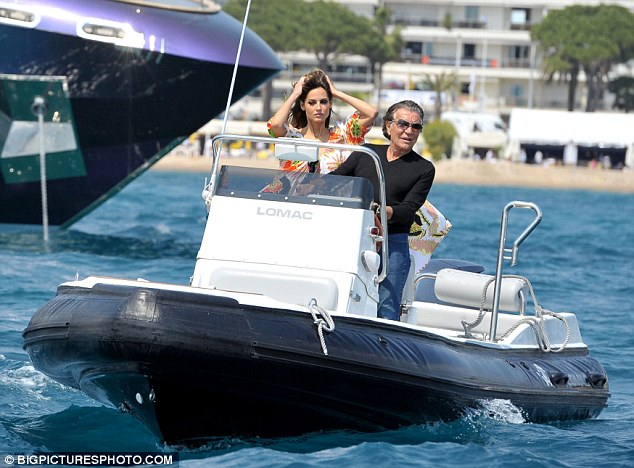 Give us a wave: Italian fashion designer Roberto Cavalli, accompanied by a young beauty, rides a speedboat nearby his yacht in Cannes on Wednesday