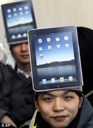 Mitsuru Endo, a Japanese fan, wears a cutout of Apple's iPad on his head in Tokyo