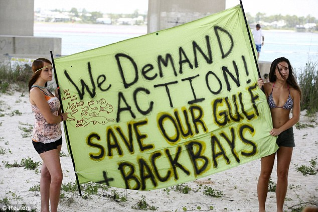 Bridget Hood and Emily Davis hold a sign demanding action in the wake of the BP oil spill