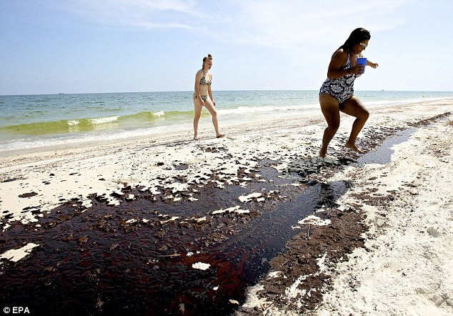 Haley Farris watches as her friend Amy Rivera steps over a pool of oil