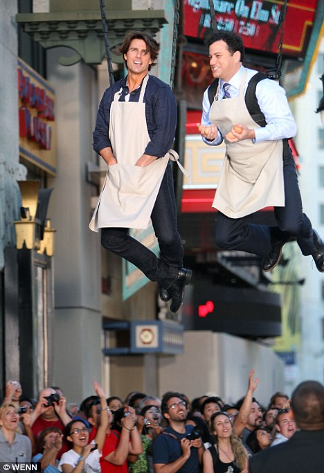 Just hanging around: The pair dangle above the heads of tourists outside the El Capitan theatre