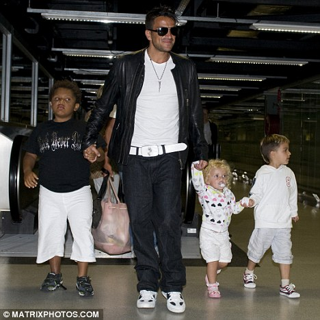 Family man: Peter, seen here with his son Junior and daughter Princess and Katie's son Harvey - who he claims he is banned from seeing