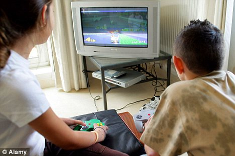 Glued to the screen: Children who spend hours every day playing video games could find it harder to concentrate at school (posed)