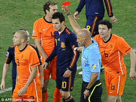 John Heitinga (L) leaves the pitch after getting a red card from English referee Howard Webb