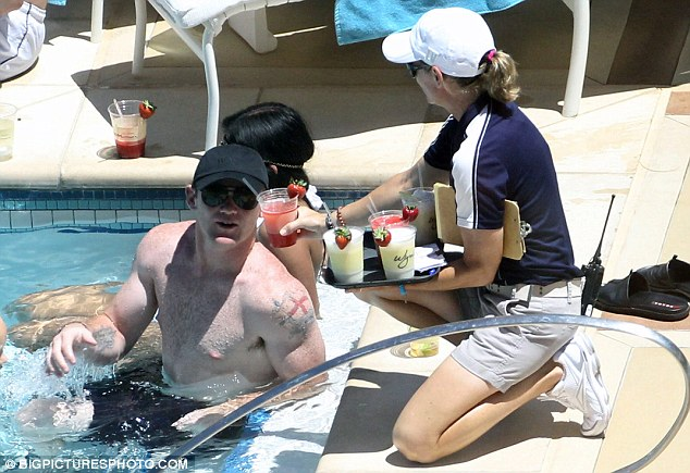 For you, sir: Wayne is served a refreshing fruit drink as he lazes about on the steps of the hotel pool