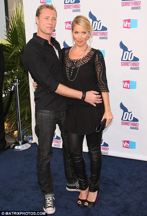 Keeping the secret: Christina Applegate wears a blousy top and  receives a bump-shielding arm from her fiance just two nights ago. Her pregnancy was announced today