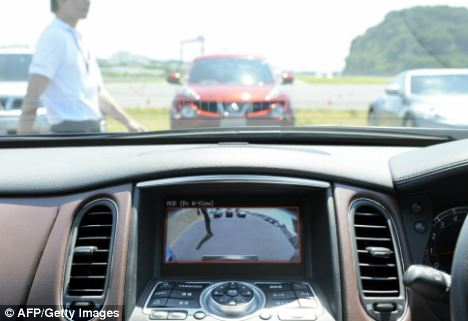 A monitor in the dashboard warns of a moving object during a demonstration of its new technology at the company's test course in Yokosuka, Japan
