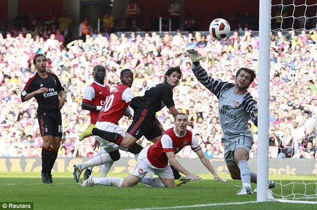 Caught napping: Alexandre Pato (third right) pounces on slapdash defending by Thomas Vermaelen (floored) to glance Clarence Seedorf's free-kick beyond Lukasz Fabianski
