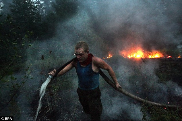 Struggle: A firefighter battles the flames near the village of Ryazanovskiy, which have already destroyed a military base and now threaten a nuclear research facility