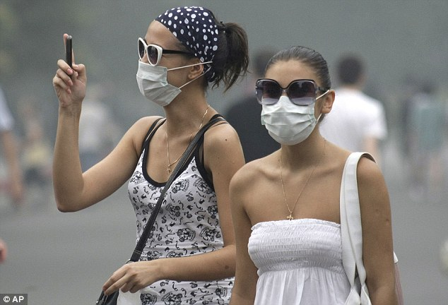 Protection: Two women wear face masks as Moscow is blanketed in thick smog from hundreds of wildfires raging across Russia