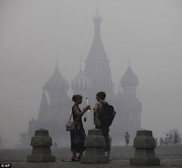 Travel chaos: St Basil's Cathedral is visible through the gloom. International flights have had to be grounded or diverted because of the fires