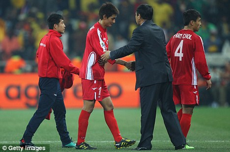 Punished: North Korea coach Kim Jong-Hun consoles one of his players after they went out of the World Cup
