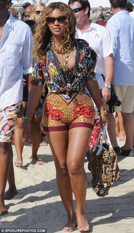 Chaotic: Beyonce makes an entrance at St Tropez's Club 55 with her tight-fitting clashing ensemble of ikat-print shirt, leopard-print bikini top and bag, and bright sequinned shorts