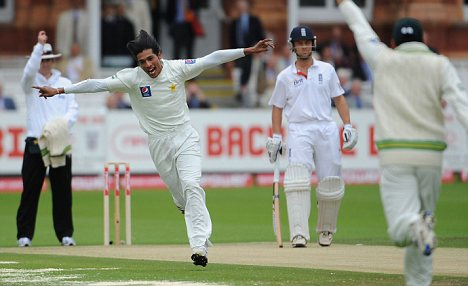 Got him: Amir celebrates taking the wicket of Cook
