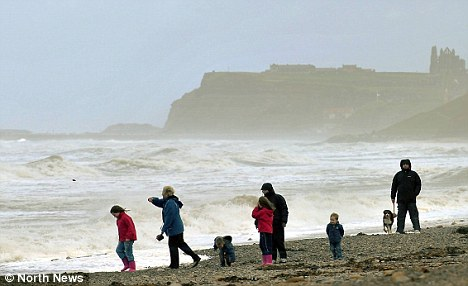 Wet and windy: Holidaymakers walk along a gloomy Sandsend beach near Whitby, North Yorkshire, over the Bank Holiday