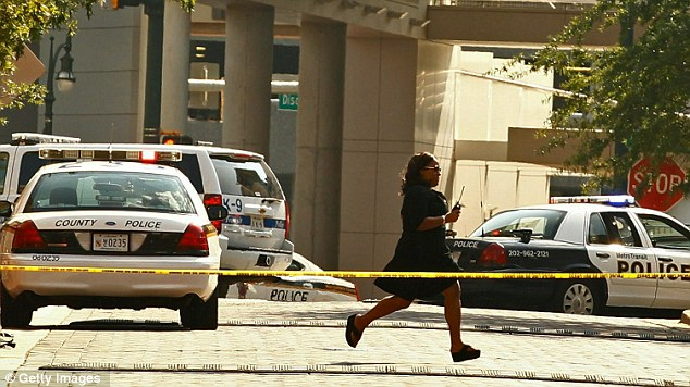 Fear: An unidentified woman runs past police cars as the hostage crisis unfolds. It is not clear if she was an employee in the building, a hostage, or working with police