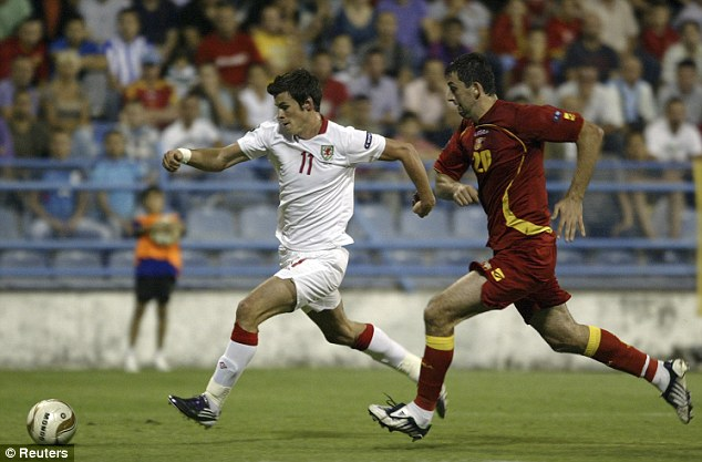 Tussle: Gareth Bale (left) is challenged by Montenegro's Miodrag Dzudovic