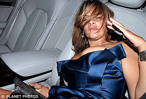 The party's over: Falling out of her dress slumped on the back seat of her car