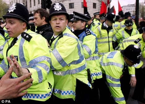 Members of the Metropolitan Police contain demonstrators, as scuffles broke out at the May Day parade in Trafalgar Square, London