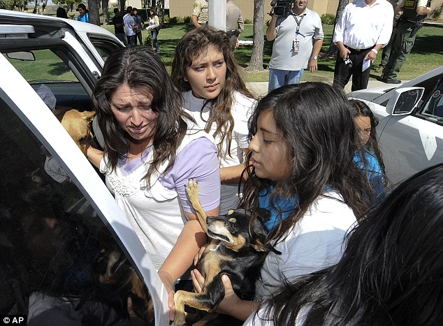 Found: Members of the 'cult' are escorted away after they were discovered alive at the Jackie Robinson Park in California today