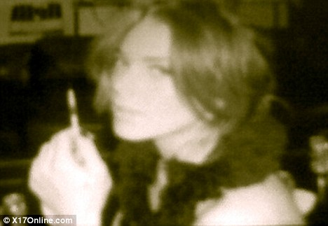 Troubled: Another image shows Lohan looking into the camera again as she holds what appears to be a syringe in front of her