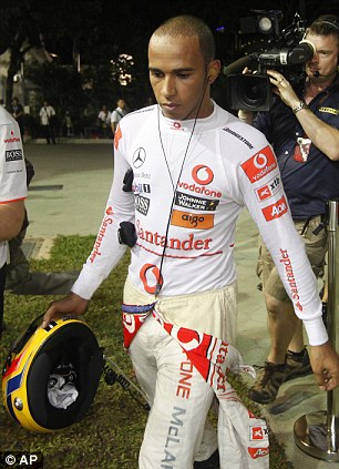 Angry: A furious Lewis Hamilton walks away after crashing out