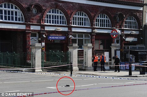 Police tape cordons off the area around Belsize Park Tube station. Circled are the handbag and other belongings of the victim