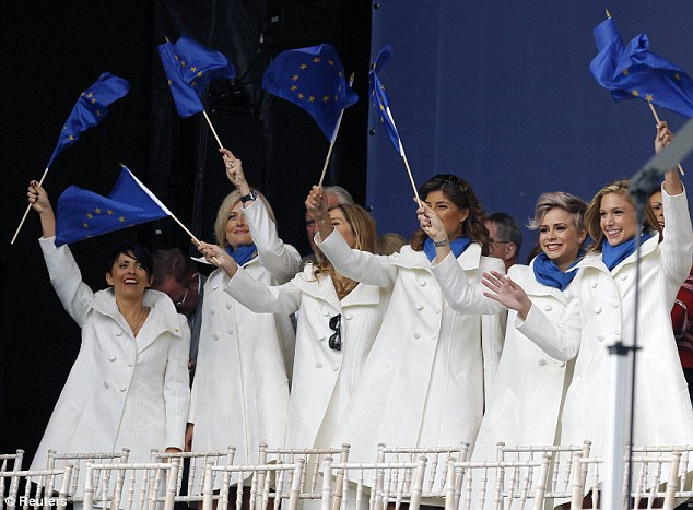 The girls are all white: The European team WAGs smile and wave their Flags of Europe as they go to take their seats