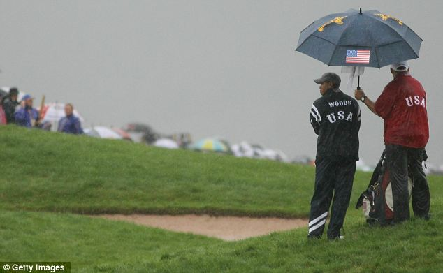 Deluge: Tiger Woods looks out mournfully from beneath an umbrella as the morning fourball matches are hit by rain
