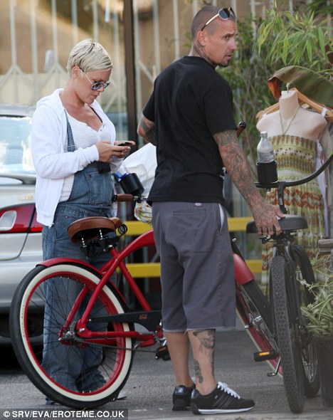 Break time: The couple take a breather from their ride, with Pink texting a friend