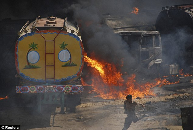 Danger: A man runs away from the site of burning oil tankers on a highway near Shikarpur, about 24 miles from Sukkur in Pakistan's Sindh province