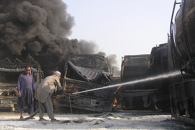 Futile: Men try to hose down one of the tankers after the Shikarpur attack
