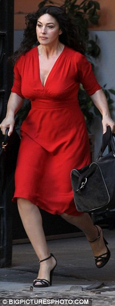 Lady in red: Seen on set later today in red, running from De Niro's character's house with her bags in hand