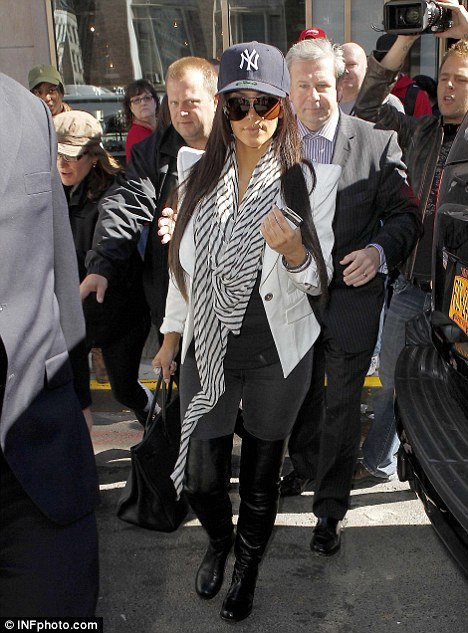 Sporting a more casual look: Kim spotted earlier today leaving her hotel in the Big Apple, wearing a New York Yankees hat, teamed with knee-high leather boots