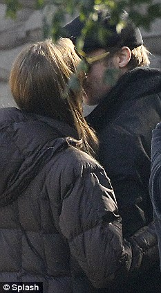 Stealing kisses: The pair snatch a romantic moment between takes