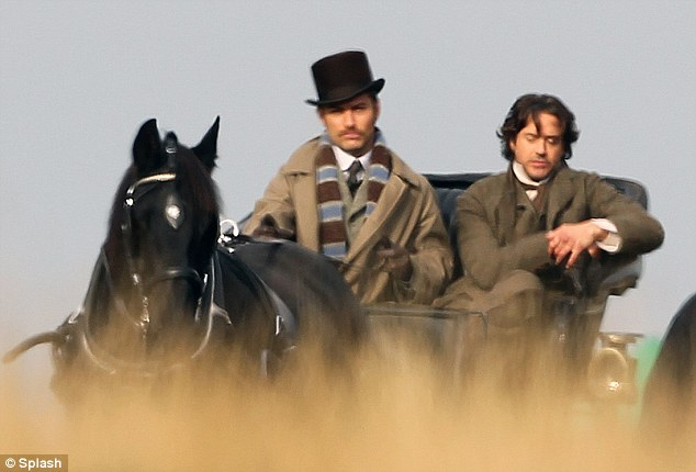 Take the reins: Jude Law drives a horse and carriage across Richmond Park in London as Robert Downey Jr sits beside him as the pair film the sequel to Sherlock Holmes today
