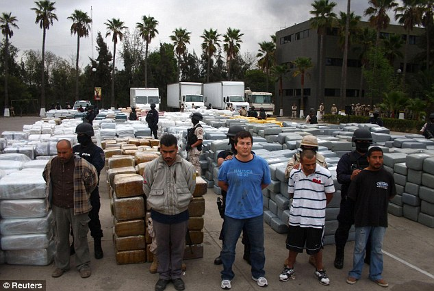 Rounded up: The suspects are shown standing before the cannabis wrapped in 10,000 brown and silver packages at a military base in Tijuana