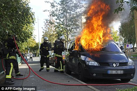 Firemen try to extinguish a burning car in Nanterre, a western suburb of Paris, during clashes over pensions reform