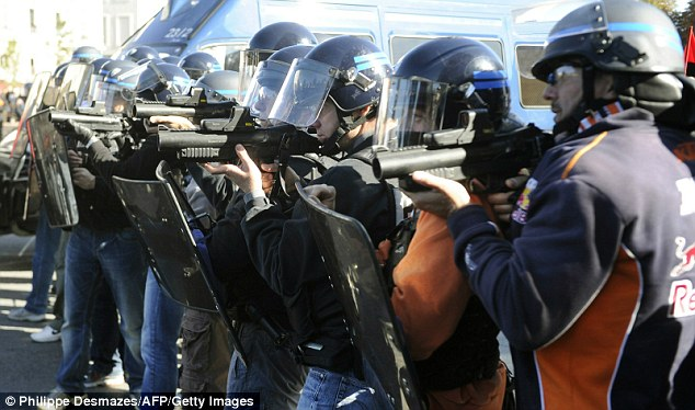 Anti-riot police officers point their flashballs at demonstrators during a protest in Lyon, southern France