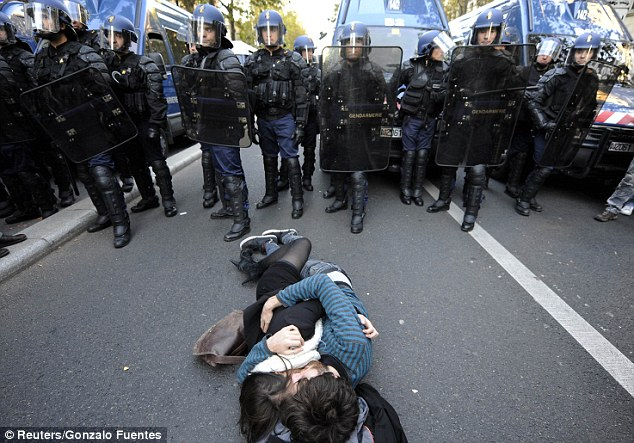 French high school students kiss on the road in front of the police at the end of a demonstration over pension reform in Paris