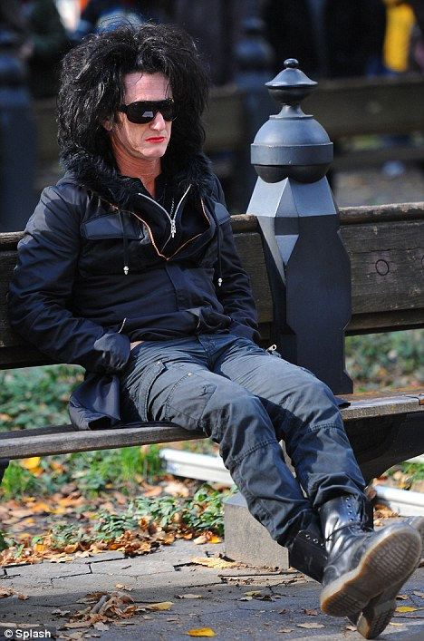 Pit-stop: A lipsticked Sean takes a rest on a new York park bench yesterday