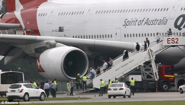 Emergency: Passengers leave the huge superjumbo after it touched down in Singapore. They are now being offered counselling